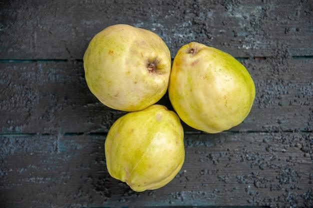 Bovenaanzicht verse kweeperen zacht en zuur fruit op de donkerblauwe bureau rijpe foetus verse boom zure plant