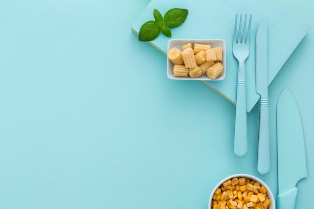 Bovenaanzicht verse maïs en bestek met kopie ruimte