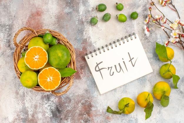 Bovenaanzicht verse mandarijnen gesneden mandarijn in rieten mand mandarijnen feykhoas fruit geschreven op kladblok op naakte achtergrond