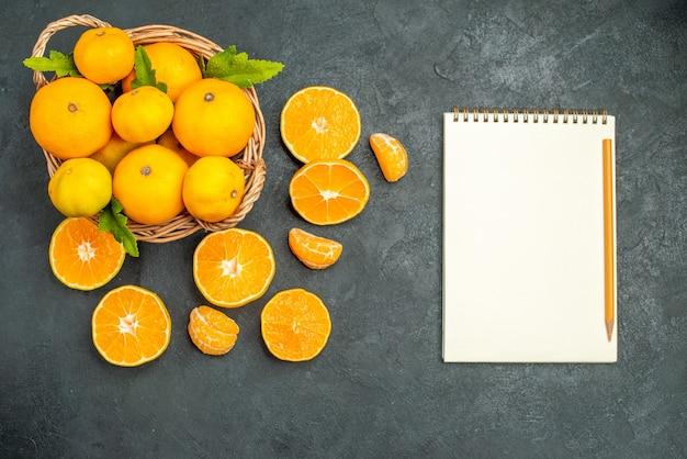 Bovenaanzicht verse mandarijnen in rieten mand een notitieboekje en potlood op donkere achtergrond