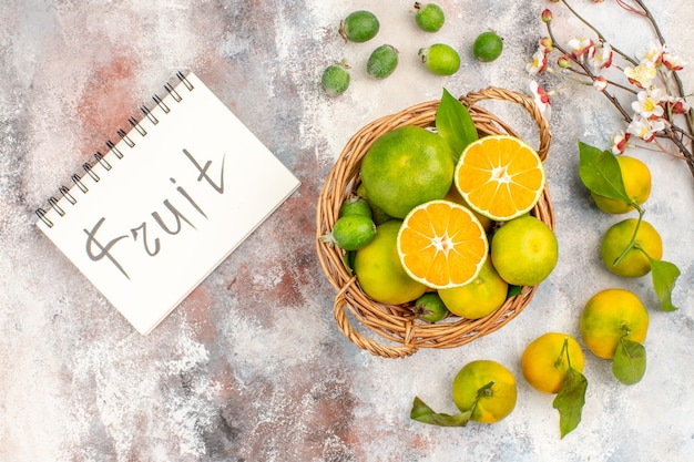 Bovenaanzicht verse mandarijnen in rieten mand mandarijnen feykhoas fruit geschreven op kladblok op naakte achtergrond