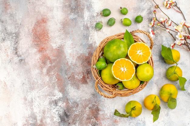Bovenaanzicht verse mandarijnen in rieten mand mandarijnen feykhoas op naakte achtergrond