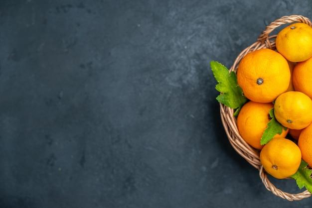 Bovenaanzicht verse mandarijnen in rieten mand op donkere achtergrond vrije plaats
