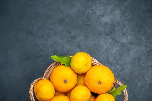 Bovenaanzicht verse mandarijnen in rieten mand op donkere achtergrond
