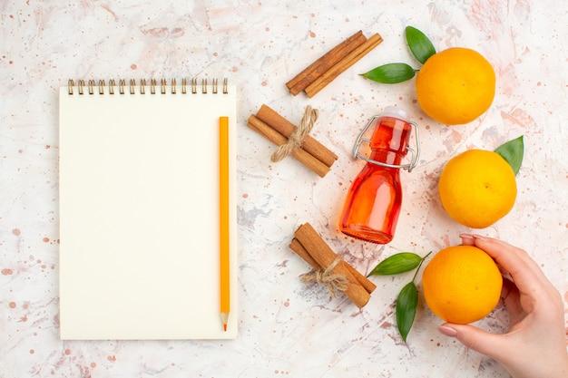 Bovenaanzicht verse mandarijnen kaneelstokjes mandarijn in vrouwelijke handfles een potlood anotebook op helder oppervlak