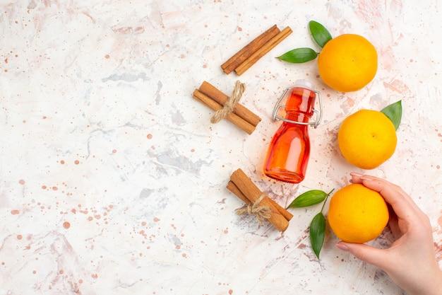 Bovenaanzicht verse mandarijnen kaneelstokjes mandarijn in vrouwelijke handfles op helder oppervlak met kopie ruimte