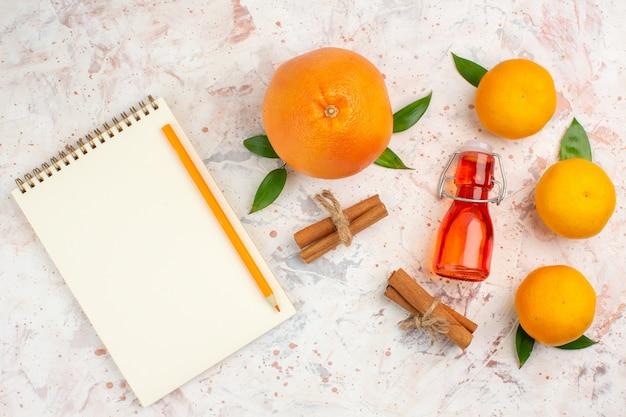 Bovenaanzicht verse mandarijnen kaneelstokjes oranje fles een potlood een notitieboekje op een helder oppervlak