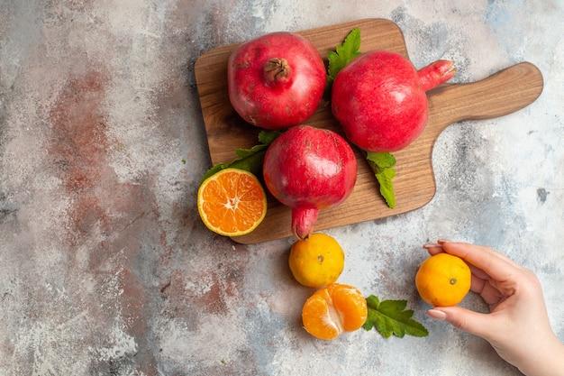 Bovenaanzicht verse mandarijnen met rode granaatappels op lichte achtergrond