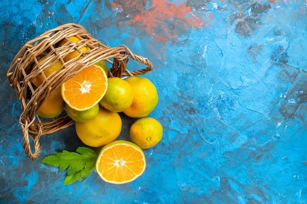 Bovenaanzicht verse mandarijnen op rieten mand op blauwe oppervlakte vrije ruimte