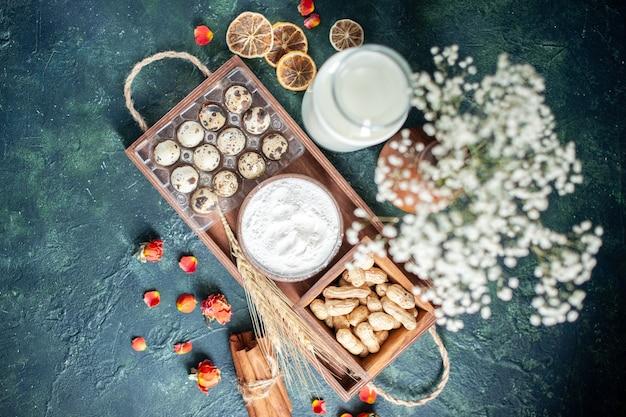 Bovenaanzicht verse melk met eieren en noten op donkerblauwe achtergrond bak cake biscuit taart deeg broodje gebak suiker