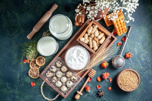 Bovenaanzicht verse melk met koekjes eieren en noten op donkerblauwe achtergrond deeg bak cake biscuit taart broodje suiker dessert