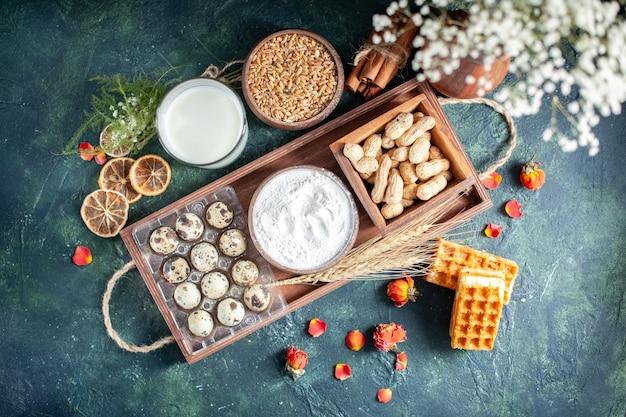 Bovenaanzicht verse melk met koekjes, noten en eieren op donkerblauwe achtergrond deeg bak cake biscuit taart thee broodje gebak suiker