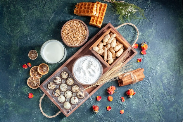 Bovenaanzicht verse melk met noten en eieren op donkerblauwe achtergrond bak cake biscuit taart thee deeg broodje gebak suiker