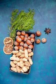 Bovenaanzicht verse noten hazelnoten en pinda's op blauwe achtergrond walnoot kleur snack cips plant boomnoot foto
