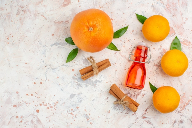 Bovenaanzicht verse oranje kaneelstokjes mandarijnen fles op heldere oppervlak vrije plaats