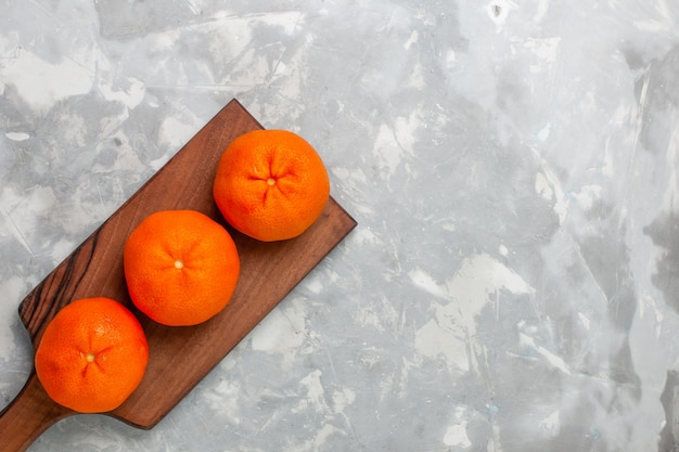 Bovenaanzicht verse oranje mandarijnen hele zure en zachte citruses op de lichte witte achtergrond.