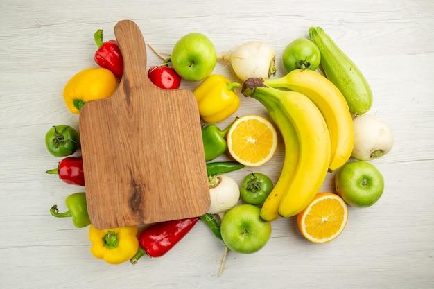 Bovenaanzicht verse paprika met bananen, appels en sinaasappel op witte achtergrond salade gezond leven foto rijp kleur dieet