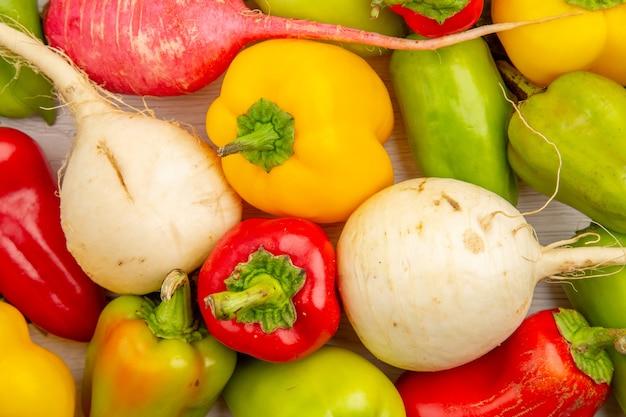 Bovenaanzicht verse paprika met radijs op witte tafel