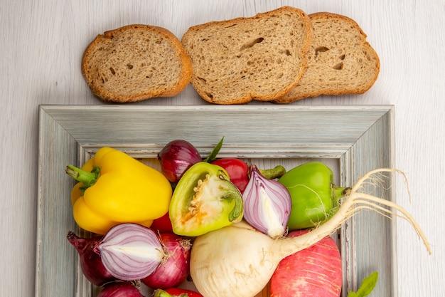 Bovenaanzicht verse paprika met radijsbroodjes en uien op witte tafel