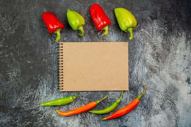 Bovenaanzicht verse paprika's met notitieblok op de lichtgrijze tafel