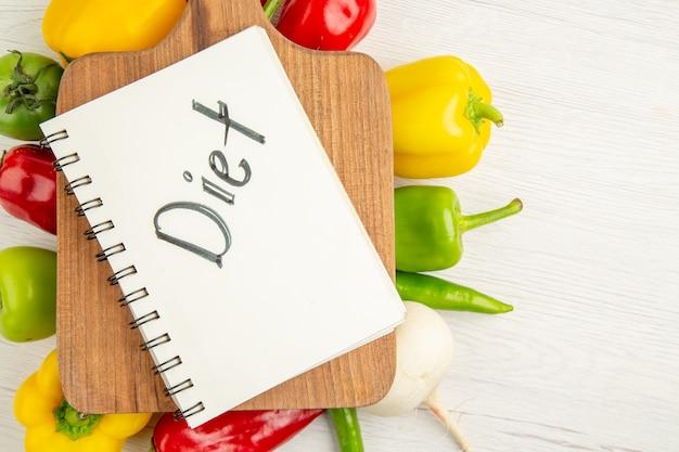 Bovenaanzicht verse paprika verschillend gekleurd met bruin houten bureau op witte achtergrond rijpe foto maaltijd kleur dieet color