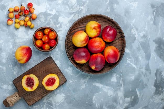 Bovenaanzicht verse perziken zacht en smakelijk fruit in bruine plaat op het licht witte oppervlak