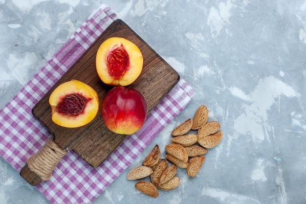 Bovenaanzicht verse perziken zacht en smakelijk fruit met noten op licht-wit bureau