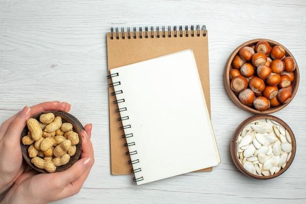 Bovenaanzicht verse pinda's met witte zaden en hazelnoten op witte tafel