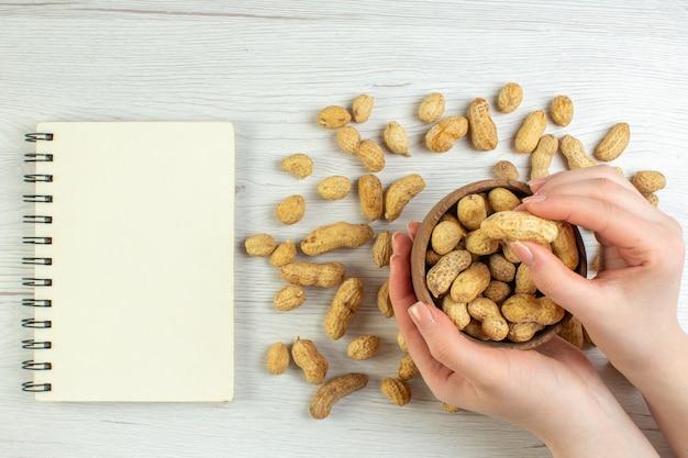 Bovenaanzicht verse pinda's op witte tafel bioscoop foto noot film zaad snack vrouwelijk