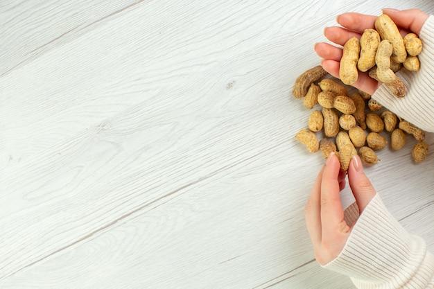 Bovenaanzicht verse pinda's op witte tafel in handen