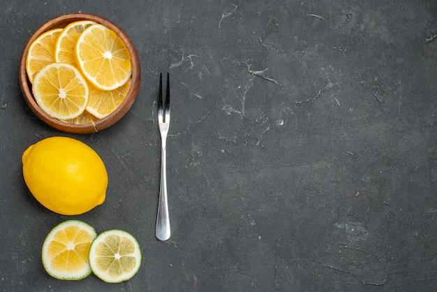 Bovenaanzicht verse plakjes citroen op donkere ondergrond