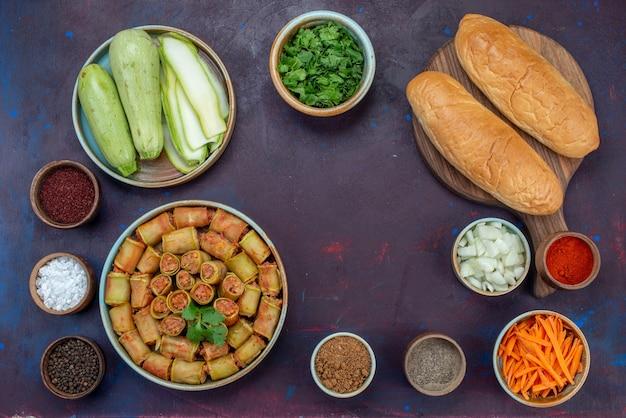 Bovenaanzicht verse pompoenen met groenten en kruiden brood vleesrolletjes op de donkerpaarse tafel vlees diner groentemaaltijd