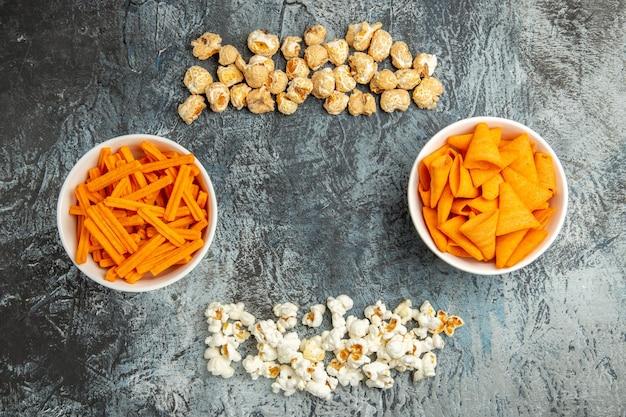 Bovenaanzicht verse popcorn met beschuit en cips op lichte ondergrond