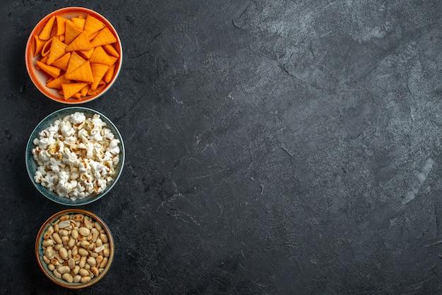 Bovenaanzicht verse popcorn met noten en chips op donkere achtergrond chips snack knapperige cracker foto