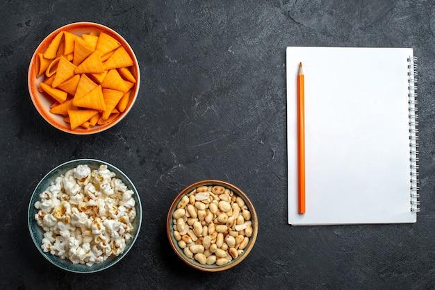 Bovenaanzicht verse popcorn met noten en chips op donkere bureau chips snack knapperige cracker