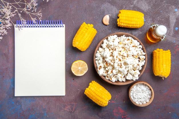 Bovenaanzicht verse popcorn met rauwe gele likdoorns en olie op de donkere oppervlakte snack popcorn maïs filmplant