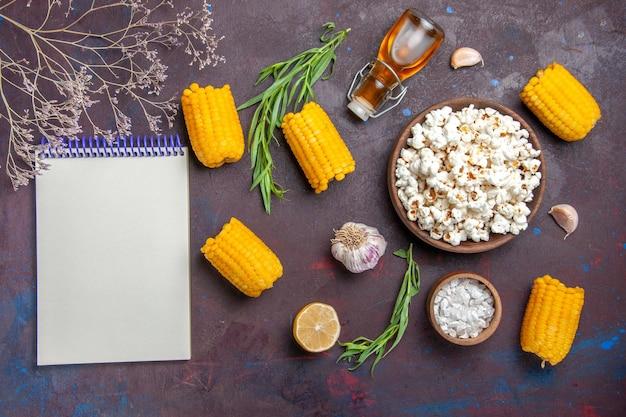 Bovenaanzicht verse popcorn met rauwe gele likdoorns op de donkere oppervlakte snack popcorn maïs filmplant