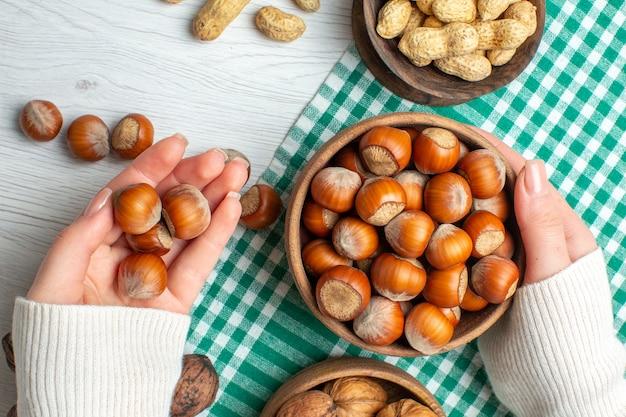 Bovenaanzicht verse rauwe hazelnoten met pinda's en walnoten op witte tafel