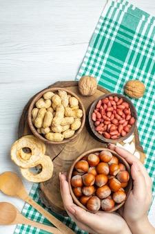 Bovenaanzicht verse rauwe hazelnoten met pinda's op witte tafel