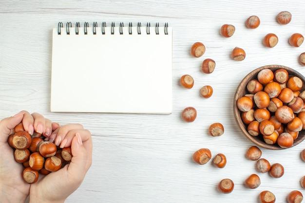 Bovenaanzicht verse rauwe hazelnoten op witte tafel in vrouwelijke hand
