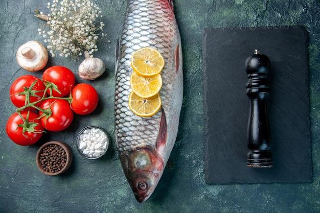 Bovenaanzicht verse rauwe vis met citroen en tomaten op donkerblauwe achtergrond