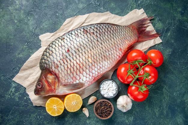 Bovenaanzicht verse rauwe vis met rode tomaten en schijfjes citroen op donkerblauwe achtergrond