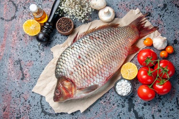 Bovenaanzicht verse rauwe vis met rode tomaten op blauwe achtergrond