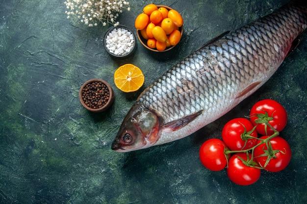Bovenaanzicht verse rauwe vis met rode tomaten op donkere achtergrond