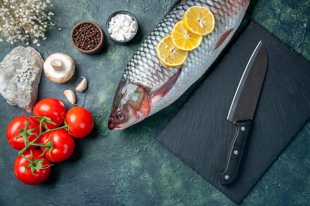 Bovenaanzicht verse rauwe vis met schijfjes citroen en tomaten op donkerblauwe achtergrond