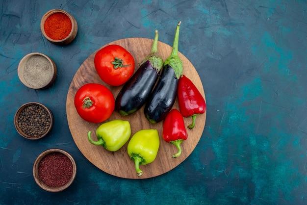 Bovenaanzicht verse rijpe groenten paprika tomaten en aubergines op donkerblauw bureau rijp plantaardig voedselmaaltijd