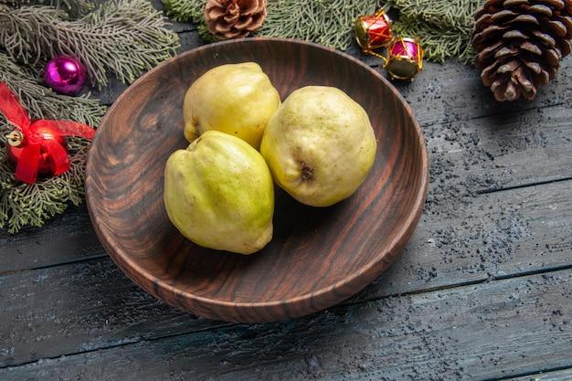 Bovenaanzicht verse rijpe kweeperen zure vruchten binnen plaat op het donkerblauwe rustieke bureau verse plant rijp boomfruit