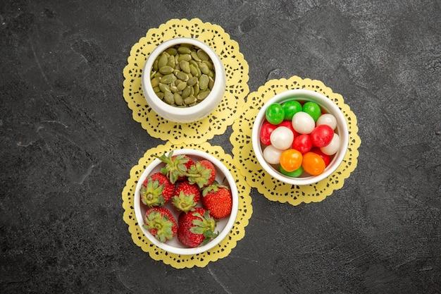Bovenaanzicht verse rode aardbeien met kleurrijke snoepjes op donkere achtergrond fruit bessen kleur regenboog snoep