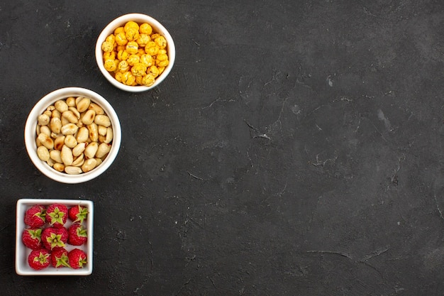 Bovenaanzicht verse rode aardbeien met noten en snoepjes op donkere oppervlakte snoep noten fruit vers