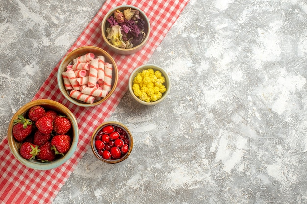 Bovenaanzicht verse rode aardbeien met snoepjes op wit oppervlak bessen vers snoep fruit